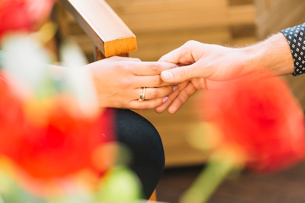 Couple tenant les mains devant une rose floue