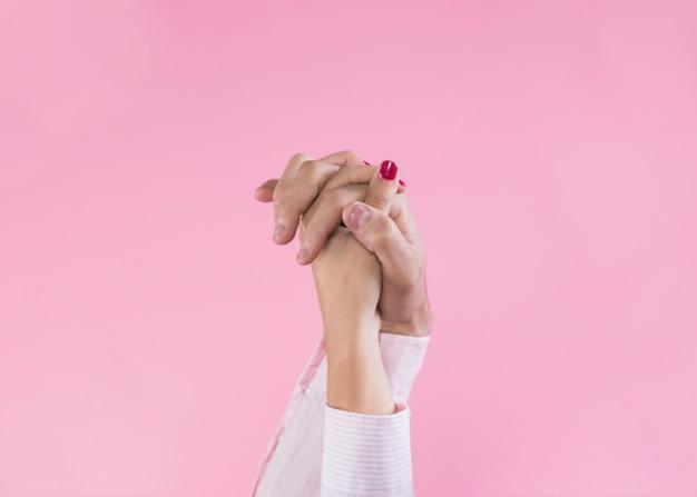 Couple tenant les mains sur fond rose