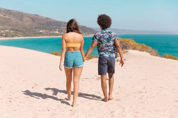Couple tenant les mains et marchant jusqu'à la mer le long de la plage avec le dos à la caméra