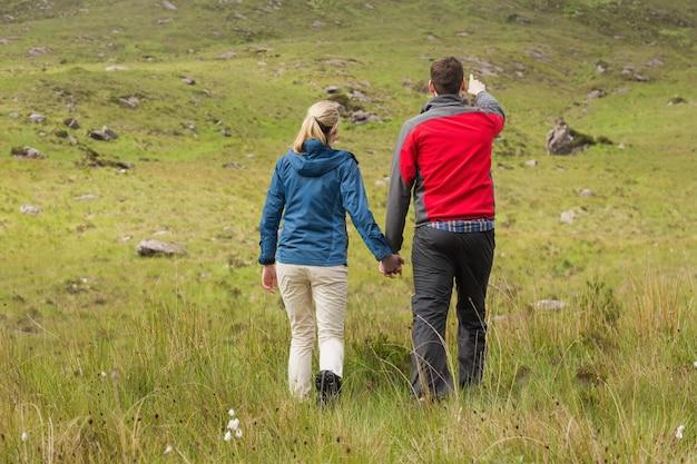Couple, tenant mains, marche, à, homme, pointage