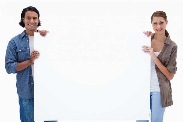 Couple tenant une pancarte blanche