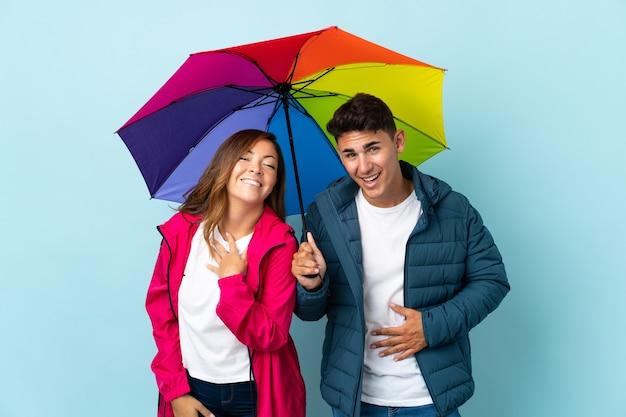 Couple tenant un parapluie bleu souriant beaucoup tout en mettant les mains sur la poitrine