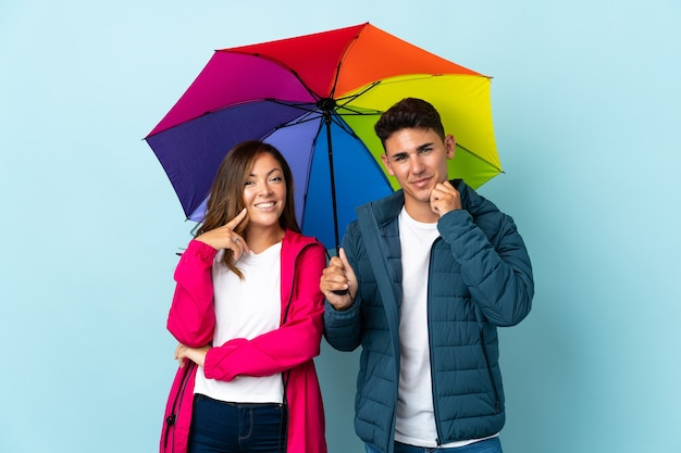 Couple tenant un parapluie bleu souriant avec une douce expression