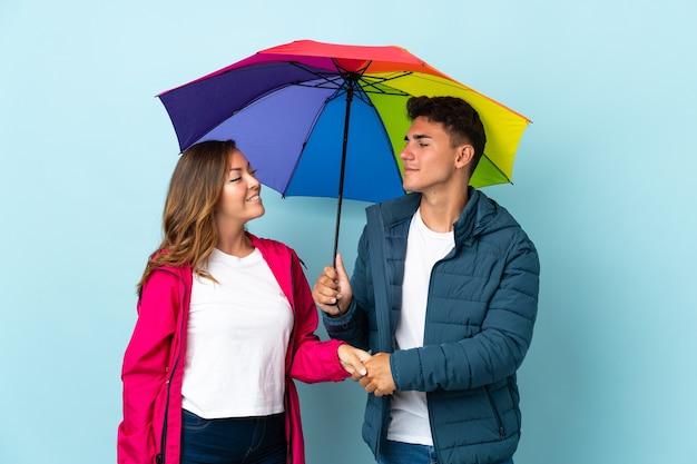 Couple tenant un parapluie sur la poignée de main bleue après une bonne affaire