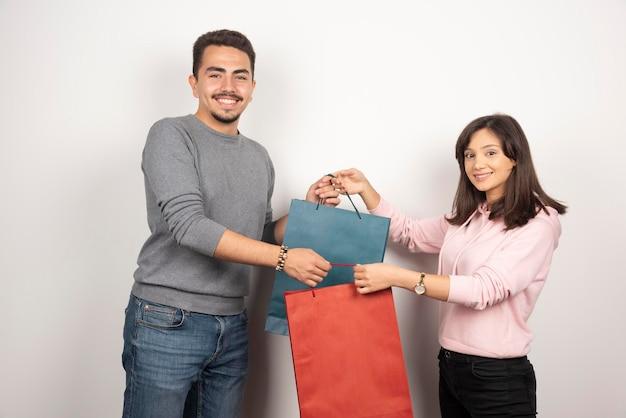 Couple tenant des sacs à provisions sur blanc.