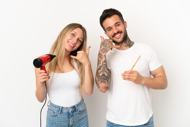 Couple tenant un sèche-cheveux et se brosser les dents sur fond blanc isolé faisant un geste téléphonique. rappelle-moi signe