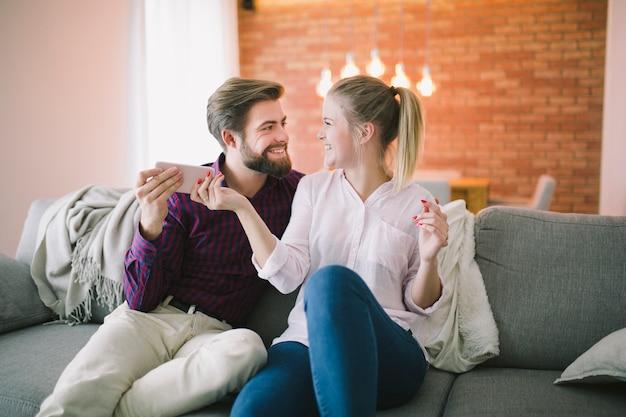 Couple tenant le smartphone sur le canapé