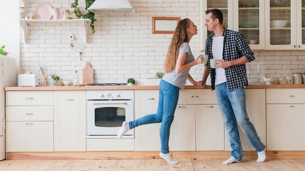 Couple tendre, boire du thé et debout dans la cuisine