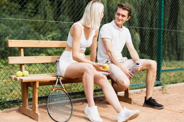 Couple de tennis assis sur le banc
