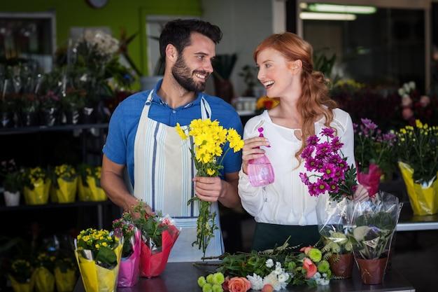 Couple, tenue, bouquet, fleurs, vaporisateur, bouteille