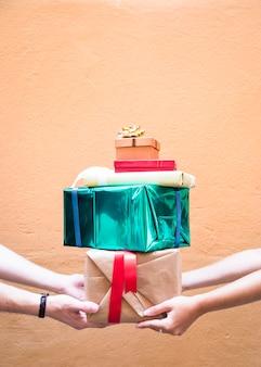 Couple, tenue, pile, de, cadeaux, contre, mur orange