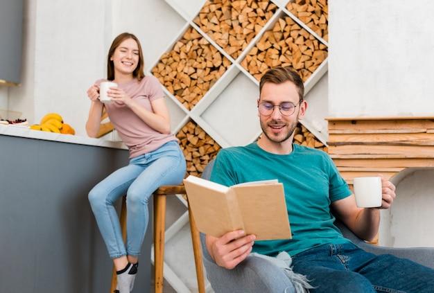 Couple, tenue, tasses, lecture, livre