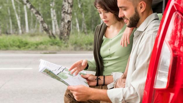 Couple de tir au milieu assis dans le coffre à la recherche sur la carte