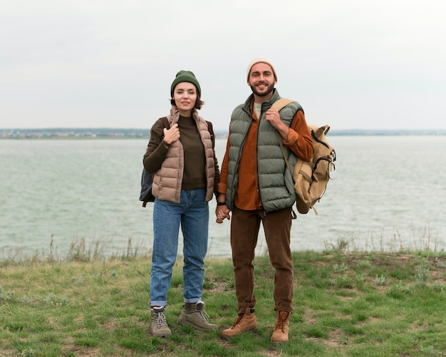 Couple de tir complet posant près de l'eau