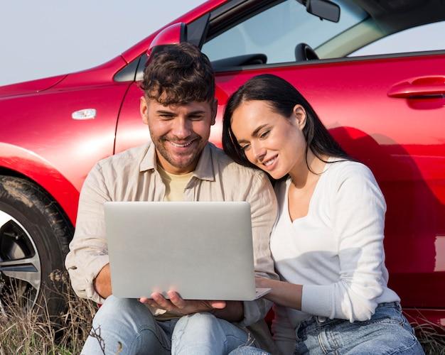 Couple de tir moyen regardant un ordinateur portable