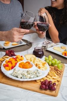 Couple toasting avec du vin et du fromage au dîner. focus sur les fromages