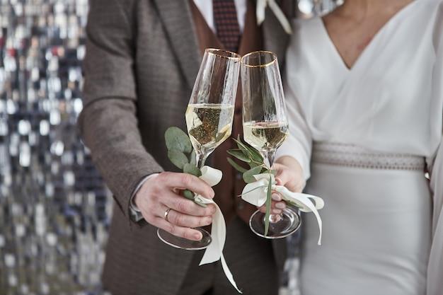 Couple toasting verres à vin pour la célébration. deux personnes tenant des flûtes faisant des acclamations