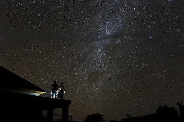 Couple sur le toit en regardant mliky way et les étoiles dans le ciel nocturne sur l'île de bali.
