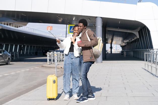 Un couple de touristes africains prend un selfie à l'aéroport