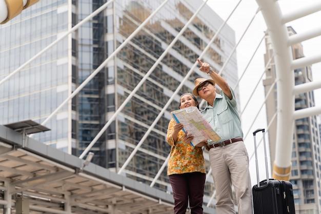 Un couple de touristes asiatiques âgés visitant joyeusement la capitale, s'amusant et regardant la carte pour trouver des endroits à visiter.