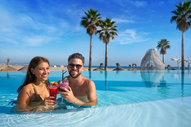 Couple de touristes ayant un bain dans une piscine à débordement sur une station balnéaire avec des cocktails