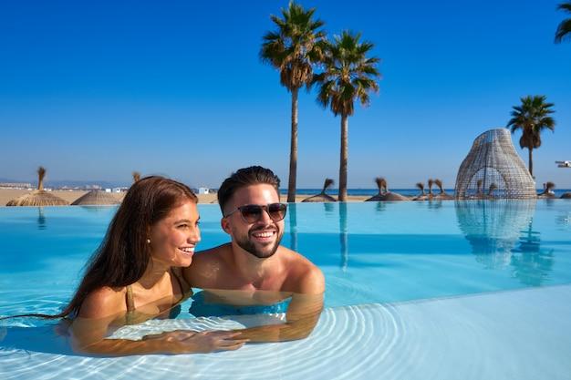 Couple de touristes ayant un bain dans la piscine à débordement
