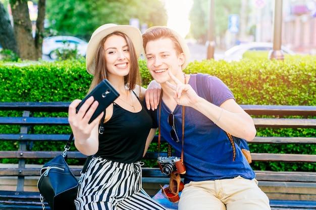 Couple De Touristes Sur Un Banc Prenant Un Selfie Photo gratuit