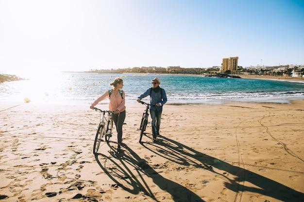 Couple de touristes avec des bicyclettes en regardant le coucher du soleil.