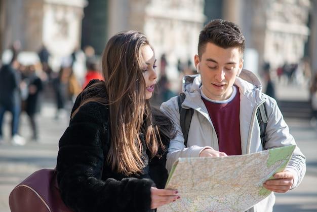 Couple de touristes dans la ville regardant une carte et discutant de la prochaine destination