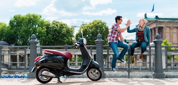 Couple de touristes faisant un arrêt pendant l'excursion vespa près de l'ancienne galerie nationale de berlin