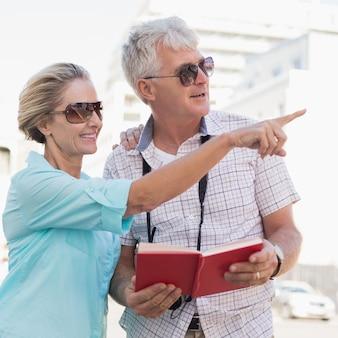 Couple de touristes heureux en utilisant le guide touristique dans la ville