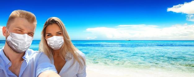 Couple de touristes avec masque de virus corona sur la plage