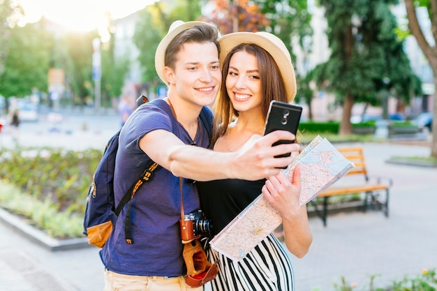 Couple de touristes prenant selfie dans le parc