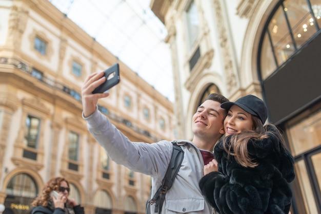 Couple de touristes prenant un selfie dans la ville de milan, italie