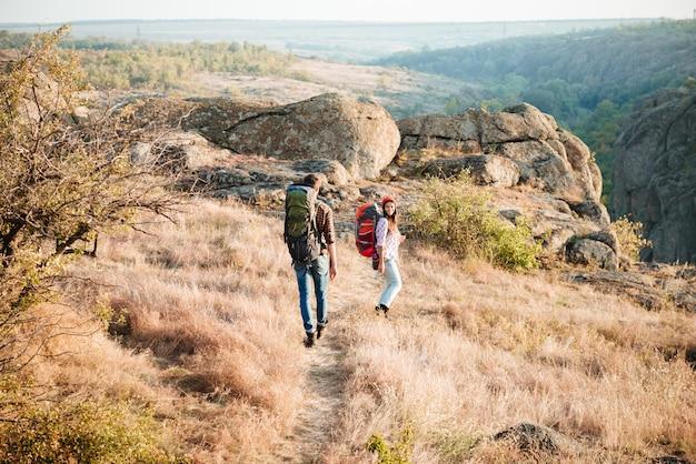 Couple de touristes sur route de montagne. vue arrière