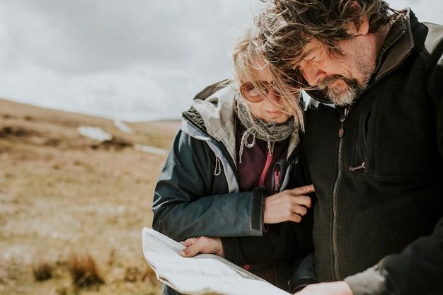 Couple de touristes senior regardant la carte tout en étant perdu au pays de galles, royaume-uni