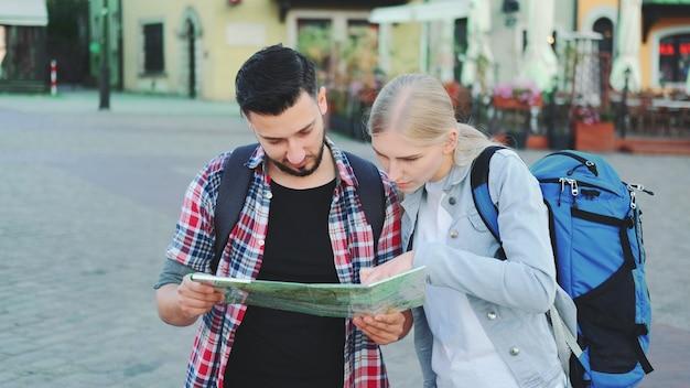Couple de touristes tenant une carte pour trouver un nouvel endroit intéressant pour faire du tourisme
