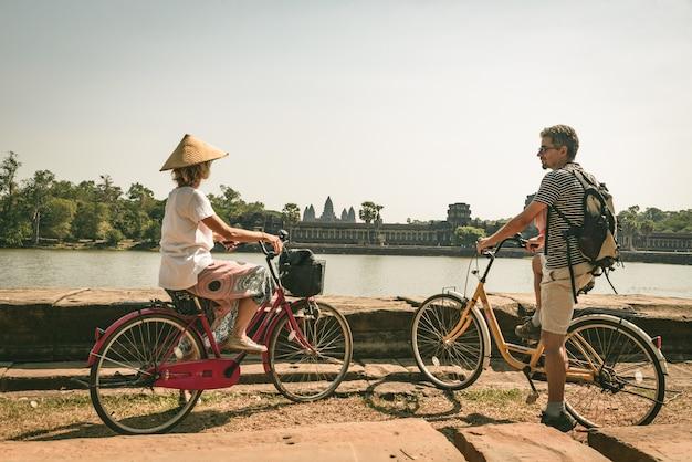 Couple de touristes à vélo dans le temple d'angkor, cambodge. la façade principale d'angkor wat se reflète sur l'étang d'eau. tourisme écologique respectueux voyageant. tonique