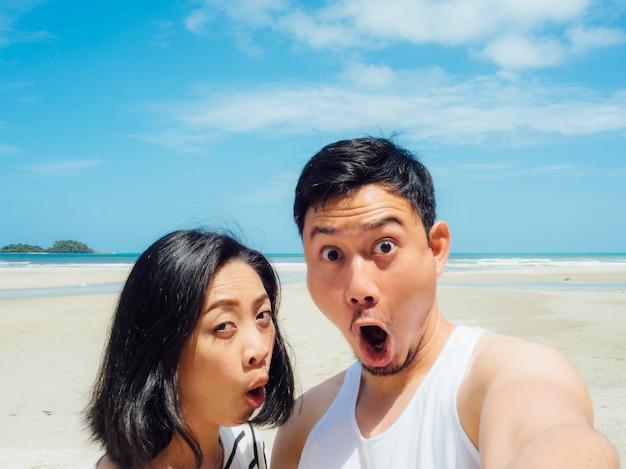 Couple touristique selfie sur la plage d'été ensoleillée