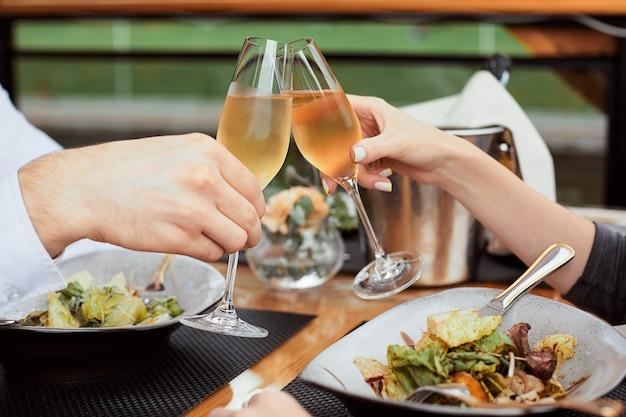 Couple en train de déjeuner et boire du champagne au restaurant en plein air.