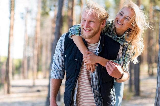 Couple en train de marcher dans les bois coup moyen