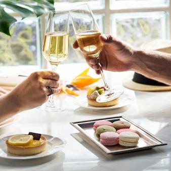 Un couple en train de sortir un verre de champagne et des desserts au restaurant