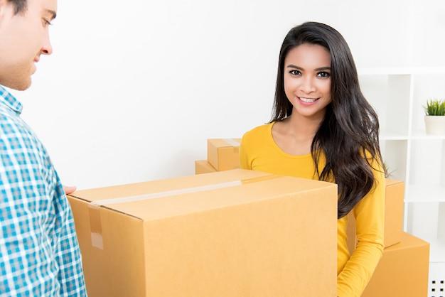 Un couple transportant une boîte ensemble emménageant dans leur nouvelle maison.