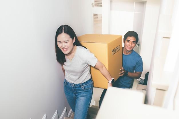 Couple transportant de lourdes boîtes en mouvement ensemble.