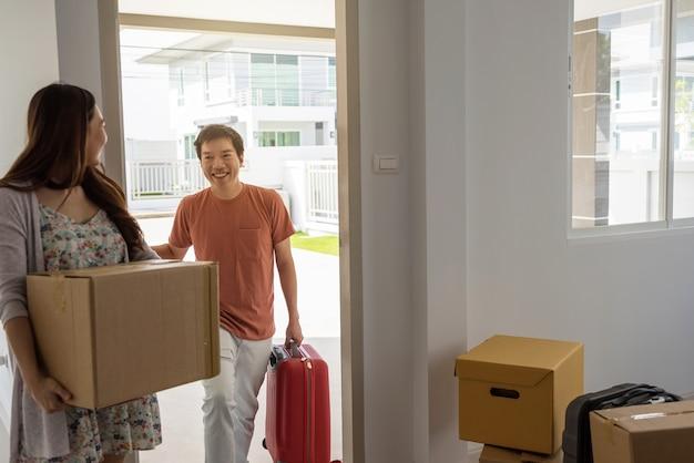 Couple transporter des boîtes de déménagement et des bagages à la nouvelle maison