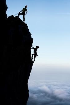 Couple de travail d'équipe grimpeurs en silhouette