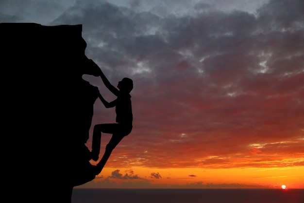 Couple de travail d'équipe randonnée s'entraider confiance confiance silhouette dans les montagnes, coucher de soleil. travail d'équipe de randonneur homme et femme s'entraider au sommet de l'équipe d'alpinisme