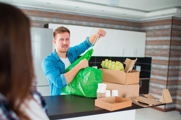 Un couple trie les ordures dans la cuisine. les déchets doivent être envoyés au recyclage. il y a beaucoup de matières recyclables. sur la table se trouvent du plastique, du verre, du fer, du papier, de vieux appareils électriques et des déchets biodégradables.