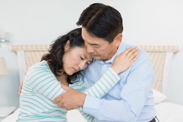 Couple triste embrassant à la maison