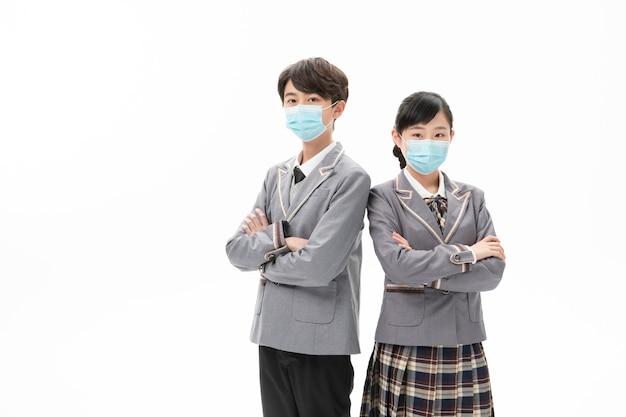 Couple en uniforme scolaire portant un masque